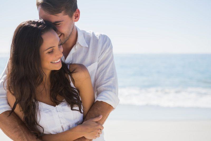 lyckliga par kramar på stranden