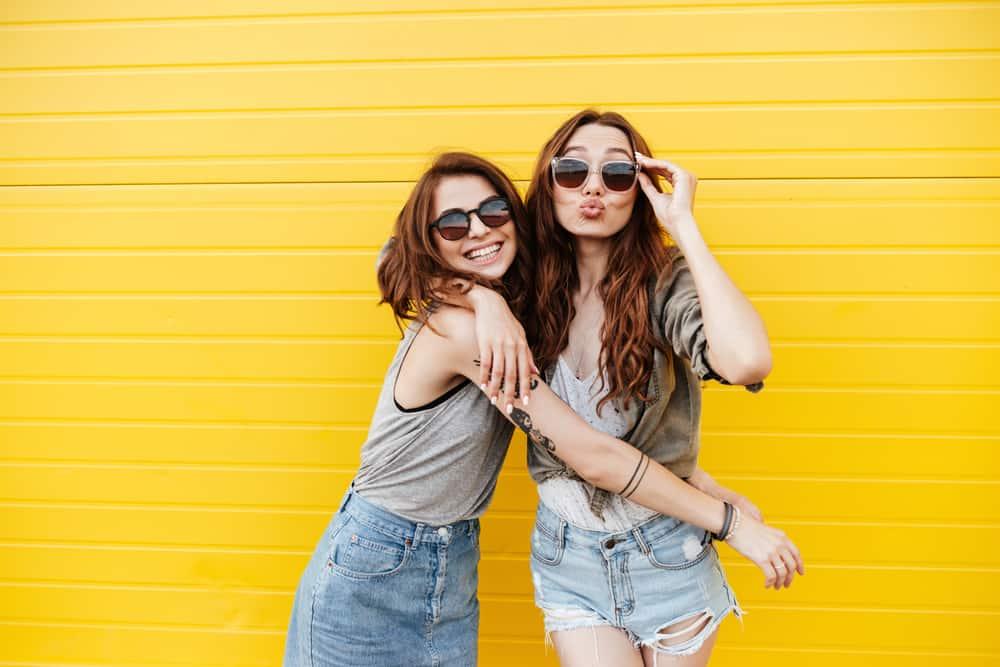 mage av två unga glada kvinnavänner som står över gul vägg