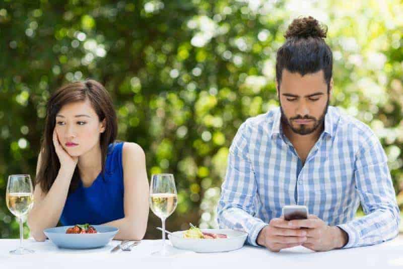 man ignorerar sin flickvän och använder telefon