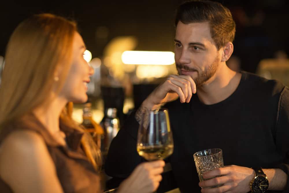 man och kvinna dricker vin och ler