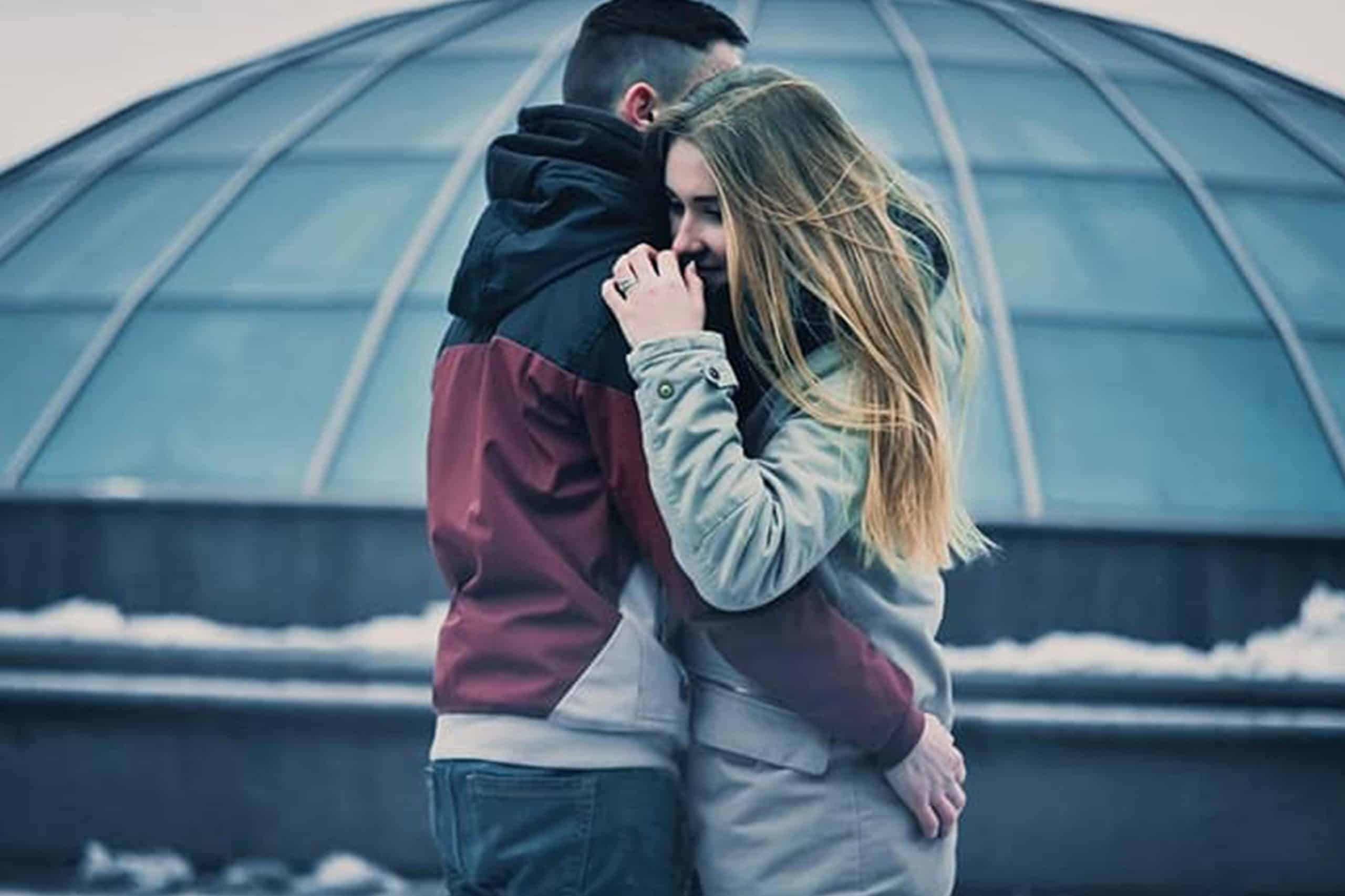 man och kvinna kram på vintern