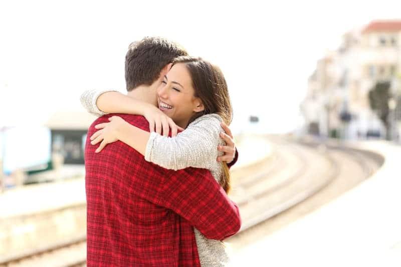 man och kvinna kram utomhus