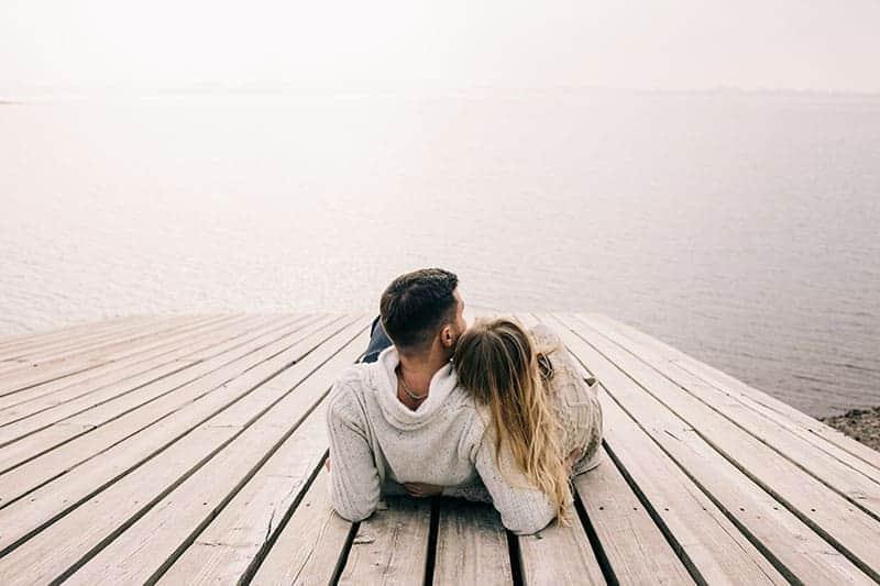 man och kvinna kramar nära sjön