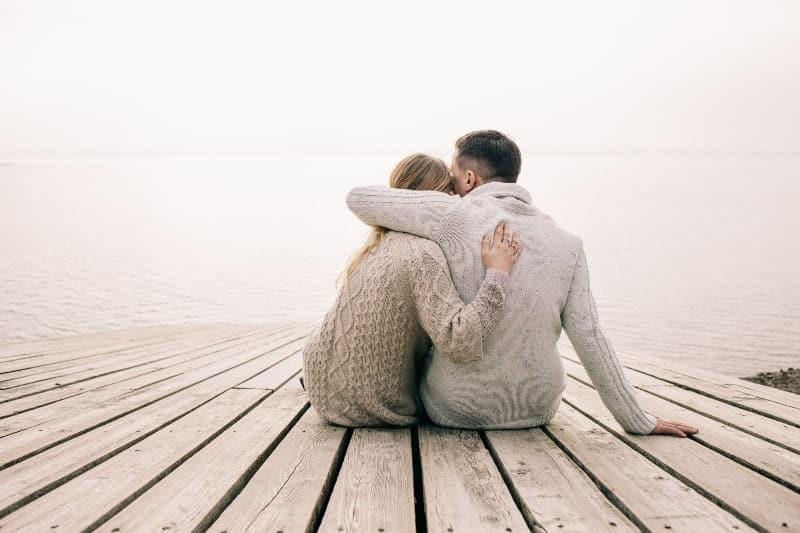 man och kvinna kramar på bryggan