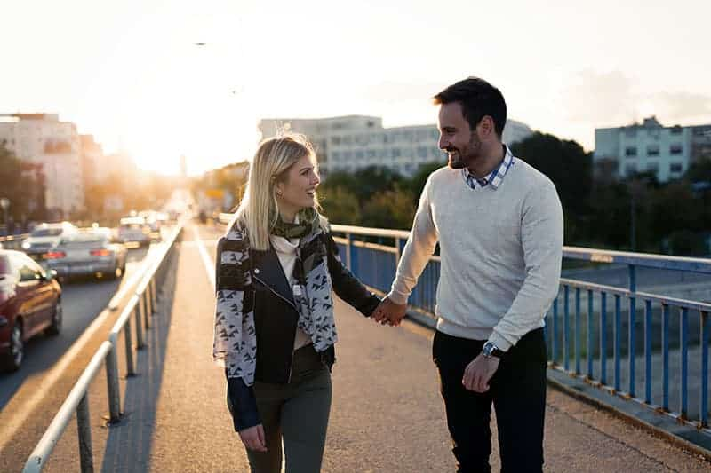 man och kvinna som håller hand och går