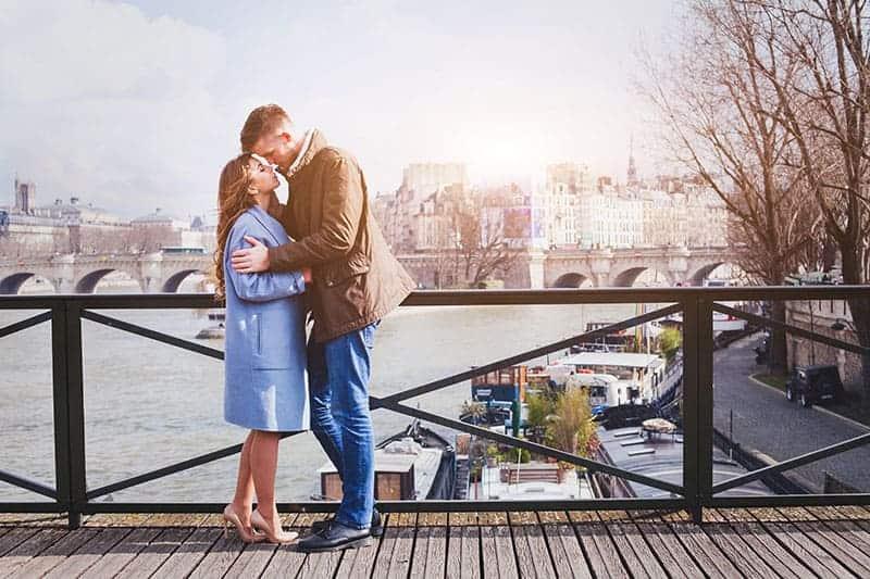 man och kvinna som kysser på bron