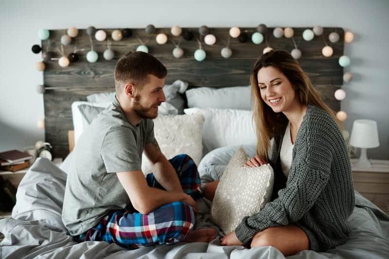 man och kvinna som sitter på sängen