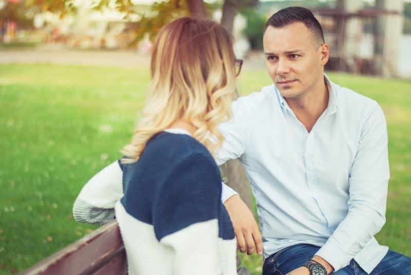 man och kvinna som sitter utomhus och pratar