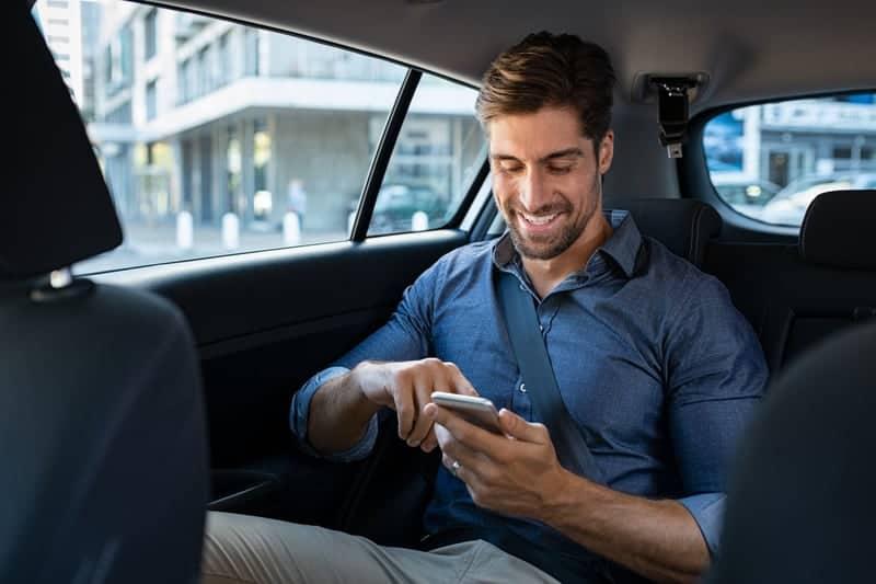 man sitter i bilen och smsar