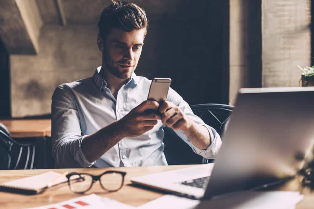 man sitter nära bärbar dator och smsar