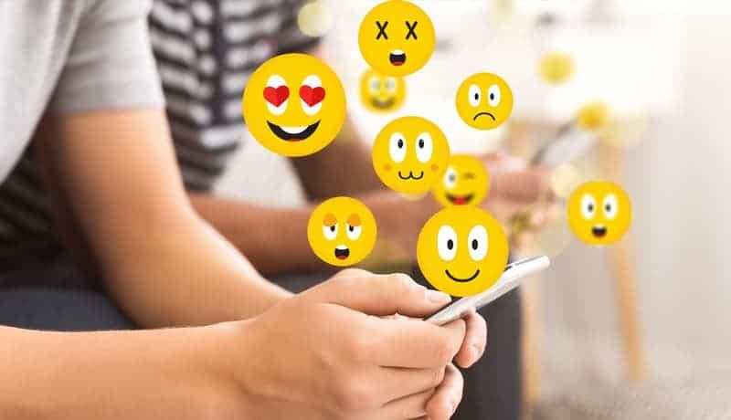 man som håller telefonen och emojis