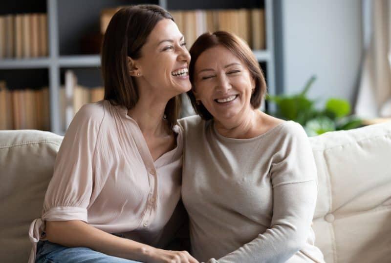 mor och vuxen dotter sitter avkopplande i soffan i vardagsrummet