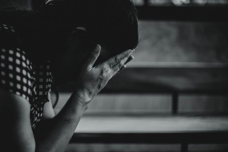 orolig asiatisk kvinna stängde ansiktet med händerna när hon satt i mörkt rum