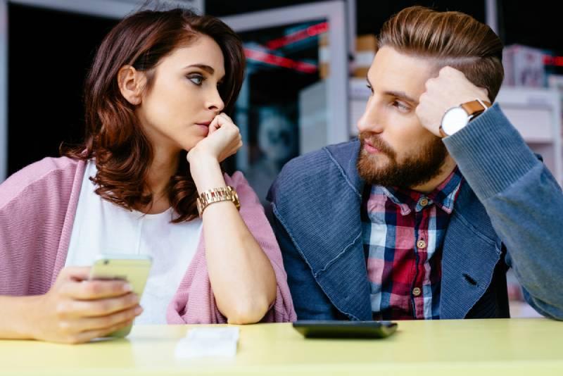 oroliga par som tittar på varandra på café