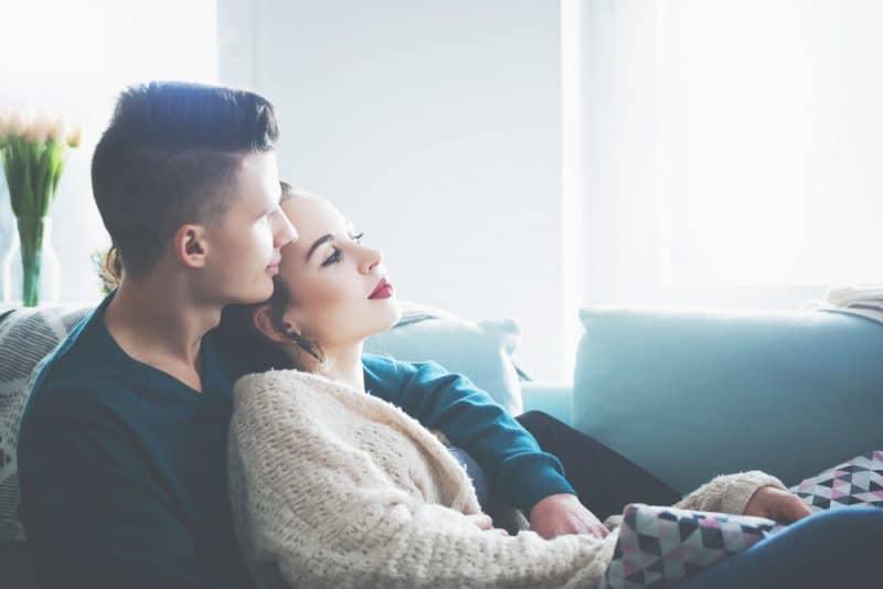 par sitter på soffan och kramar