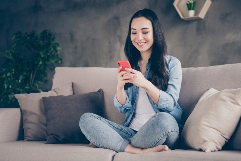 positiv glad tjej sir divan ben korsade använda smartphone läsa sociala nätverk