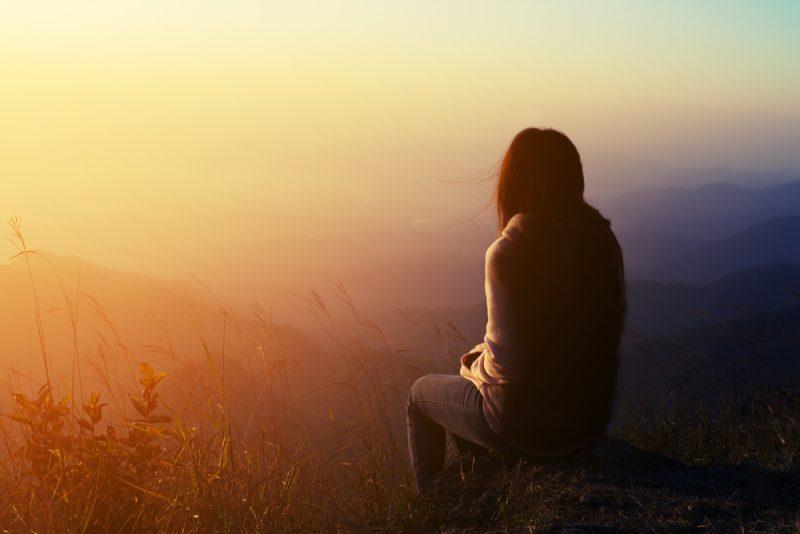 siluett kvinna sitter på berg på morgonen och vintage filter