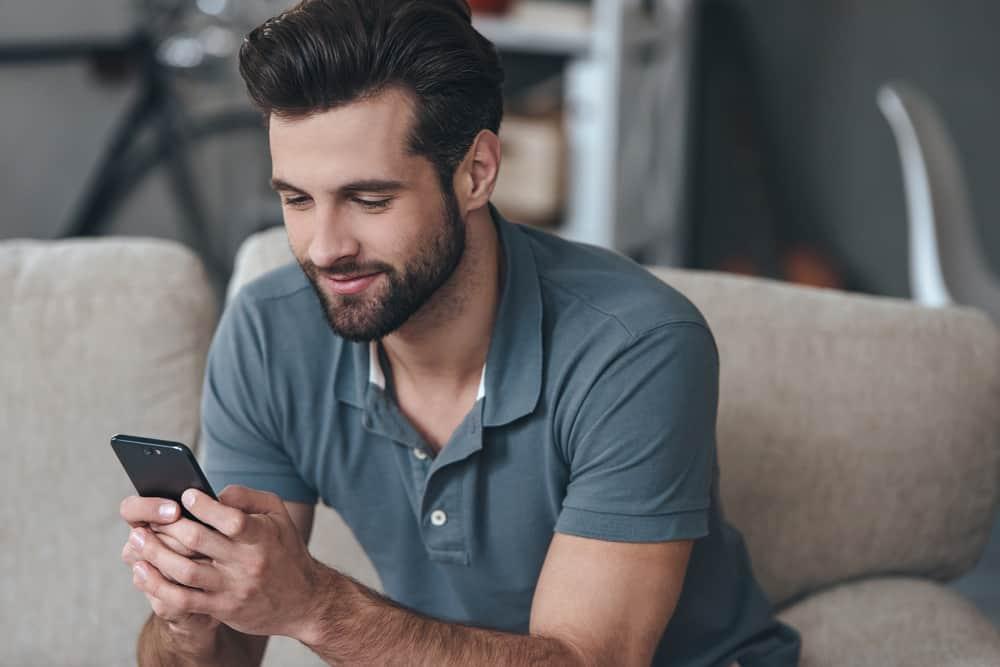 ung man använder sin smartphone medan du sitter i soffan