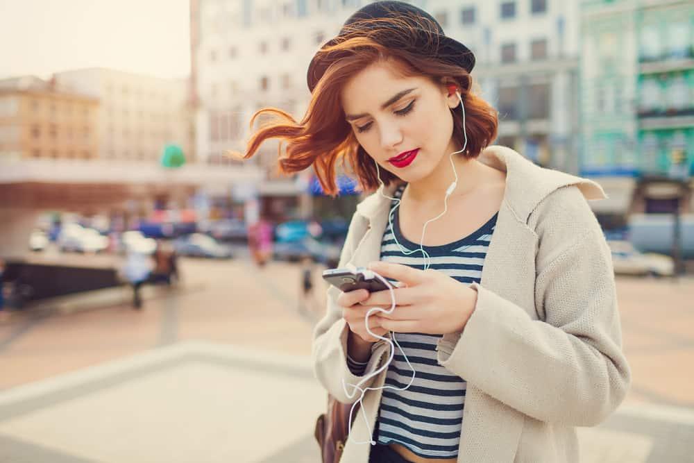 ung snygg vacker kvinna med hatt som använder sin telefon