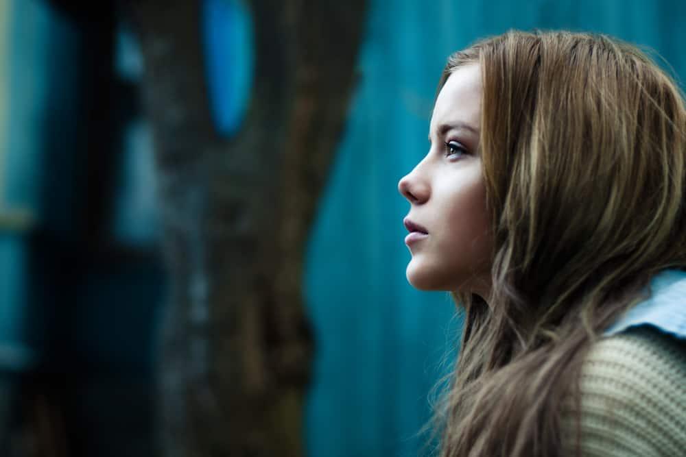 vacker kvinna ensam med blå vägg i bakgrunden
