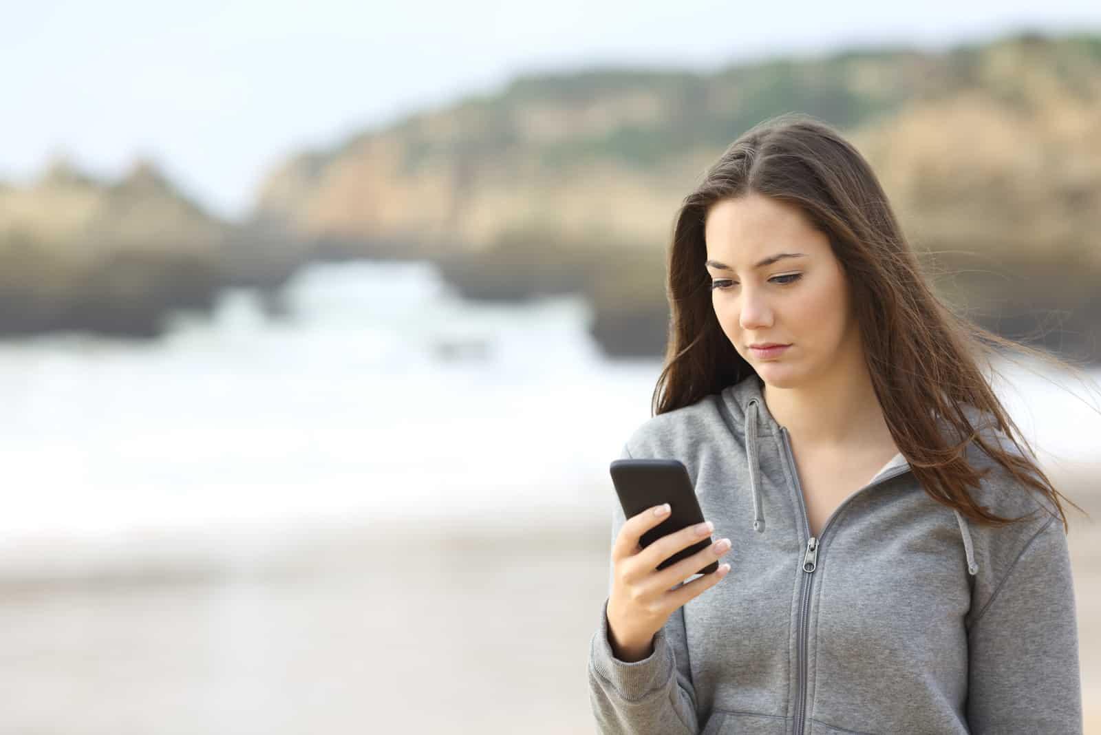 kvinna att skriva på sin telefon utanför