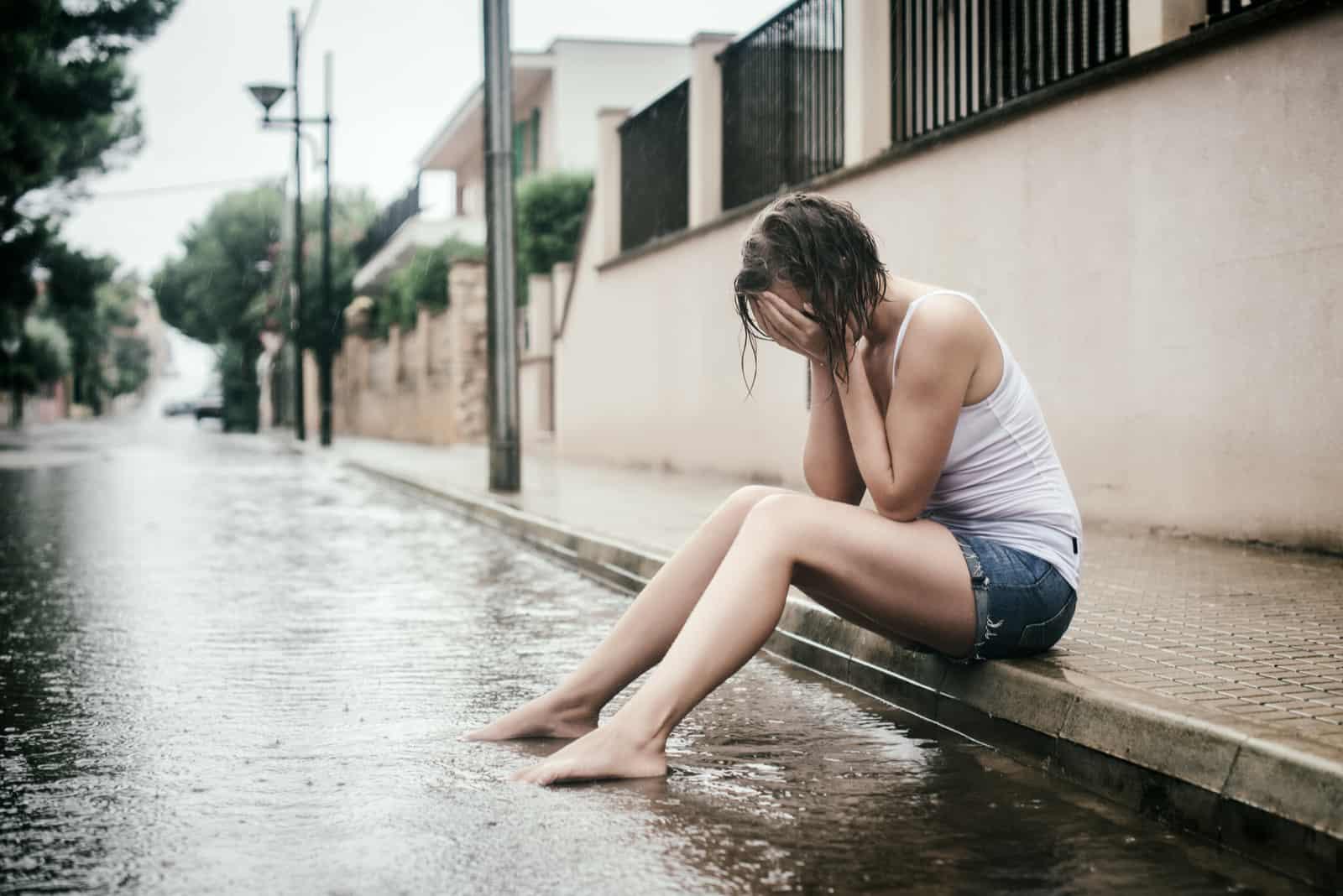 en sorglig kvinna sitter på trottoaren i regnet och gråter