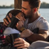 Pojkvän som kysser hans le flickvän i pannan
