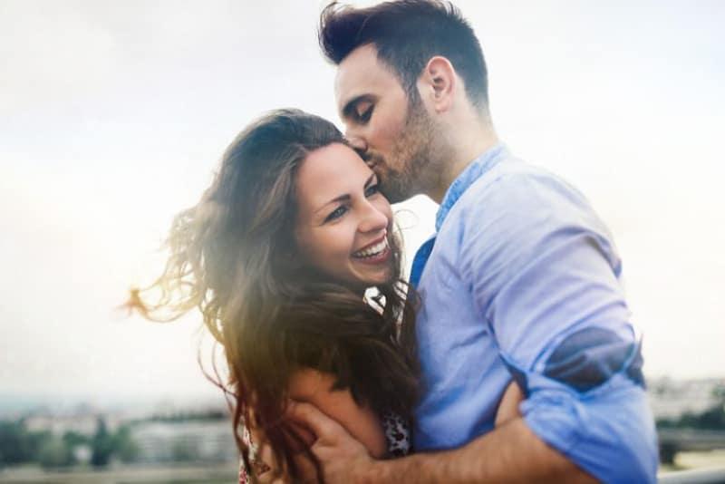 en man som kysser en tjej i pannan