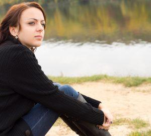 fundersam kvinna som sitter ensam utomhus