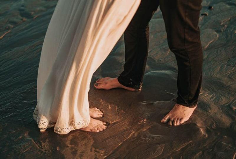 manliga och kvinnliga fötter i sanden