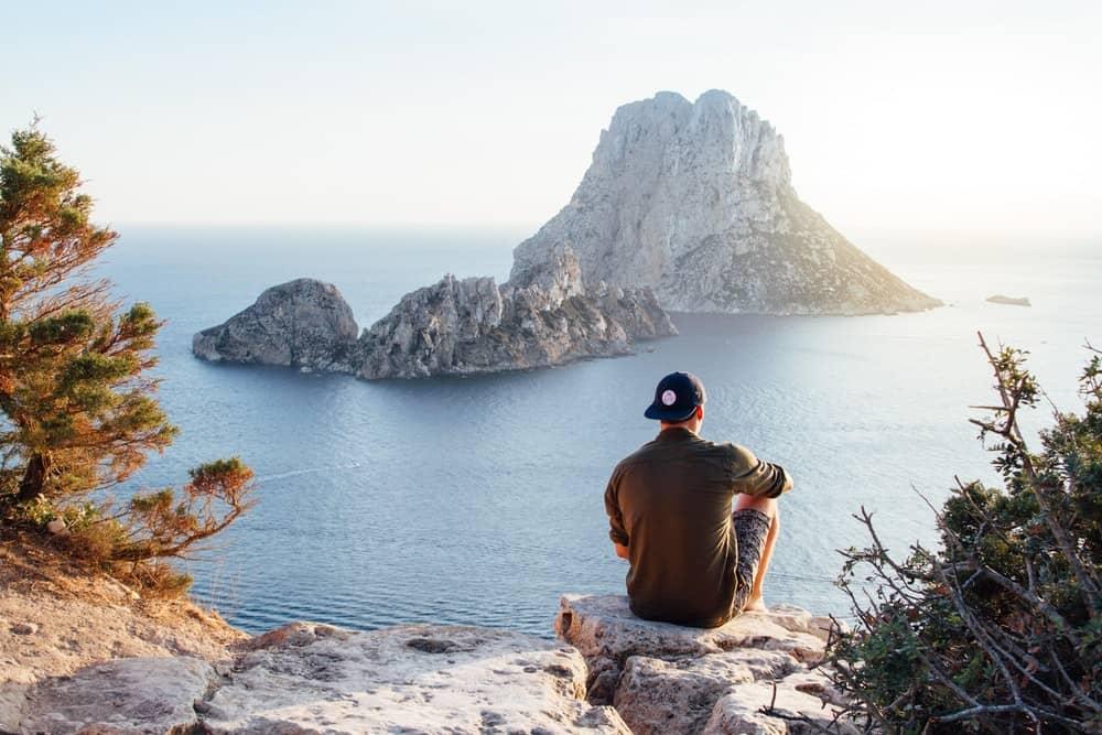 ensam kille med mössa sitter och tittar på havet