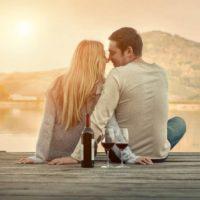 romantiska par sitter framför sjön vid solnedgången