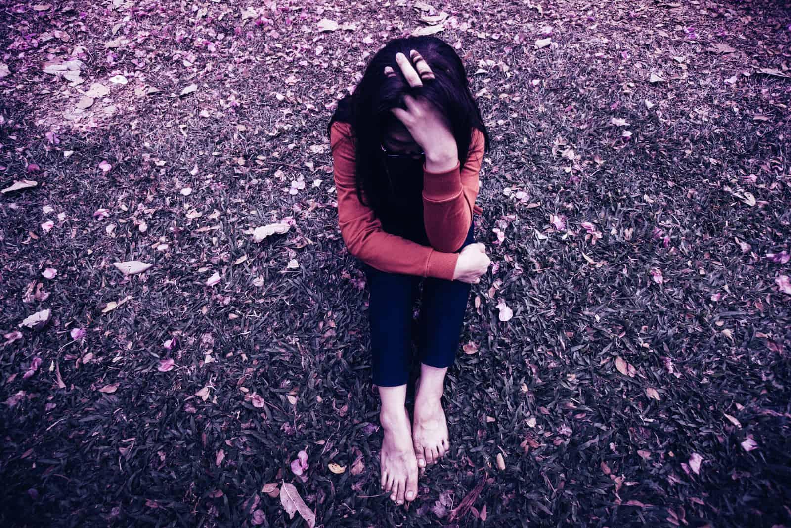 en sorglig barfota flicka som sitter på gräset