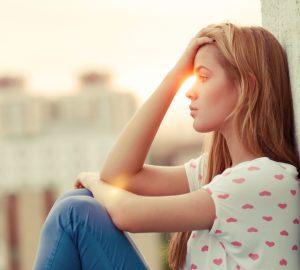 vacker sorglig blond kvinna sitter