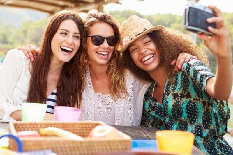 Flickvänner som tar selfies under lunch utomhus