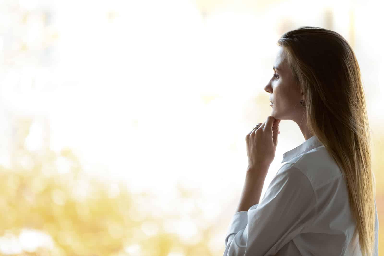 Fundersam drömmande affärskvinna som ser genom kontorsfönster