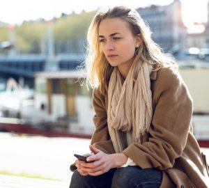 fundersam och ledsen blond kvinna som sitter ensam