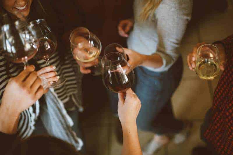 Grupp av vänner som hejar med exponeringsglas av vin