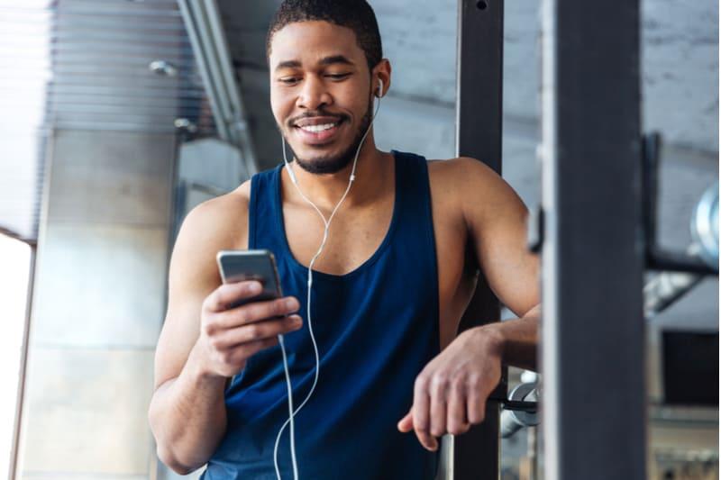 en leende svart man i gymmet använder en smartphone