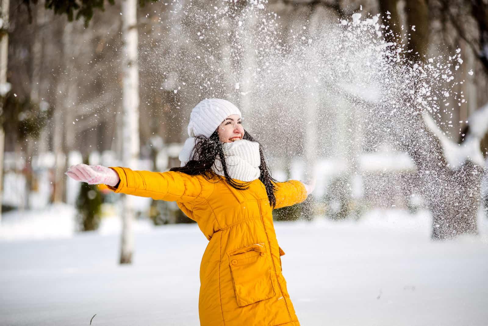 en ung kvinna i en gul jacka har kul i snön