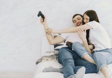 älskande par som sitter på sängen och spelar lekstation