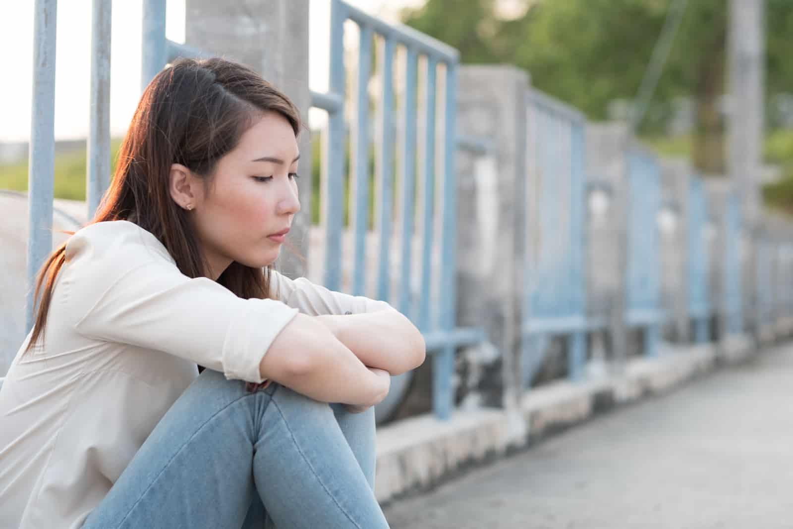 ledsen kvinna som sitter utanför