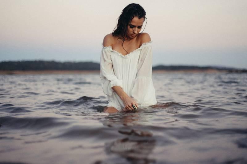 Kvinna som poserar i vattnet