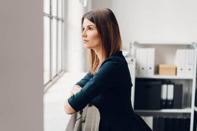 Smuk kvinde stående og stirrer ud af et vindue