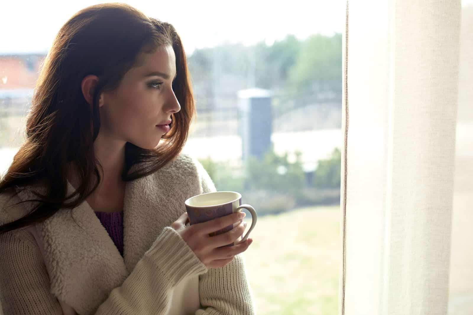 fundersam kvinna som håller en kopp kaffe