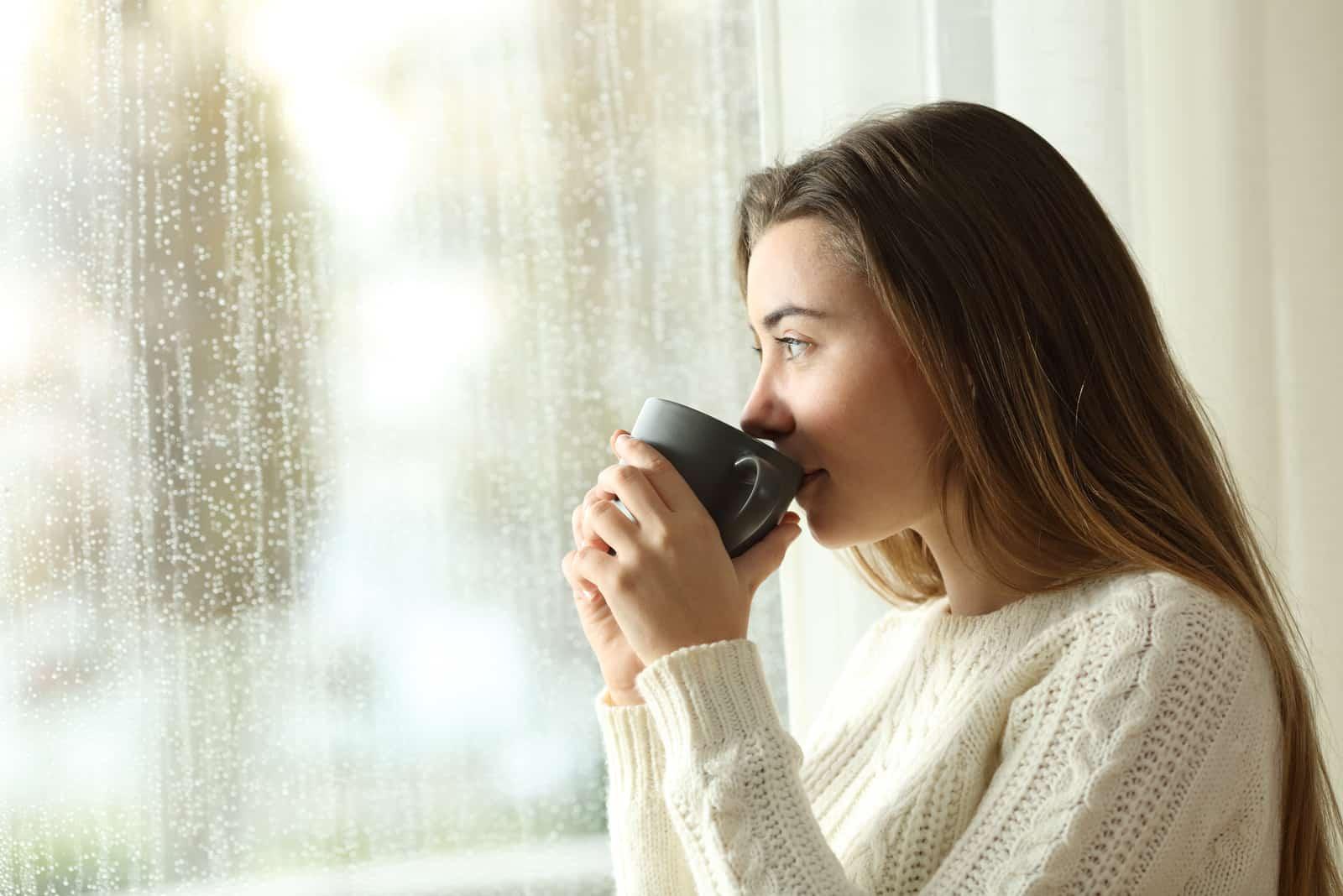 kvinna dricka kaffe tittar utanför genom ett fönster