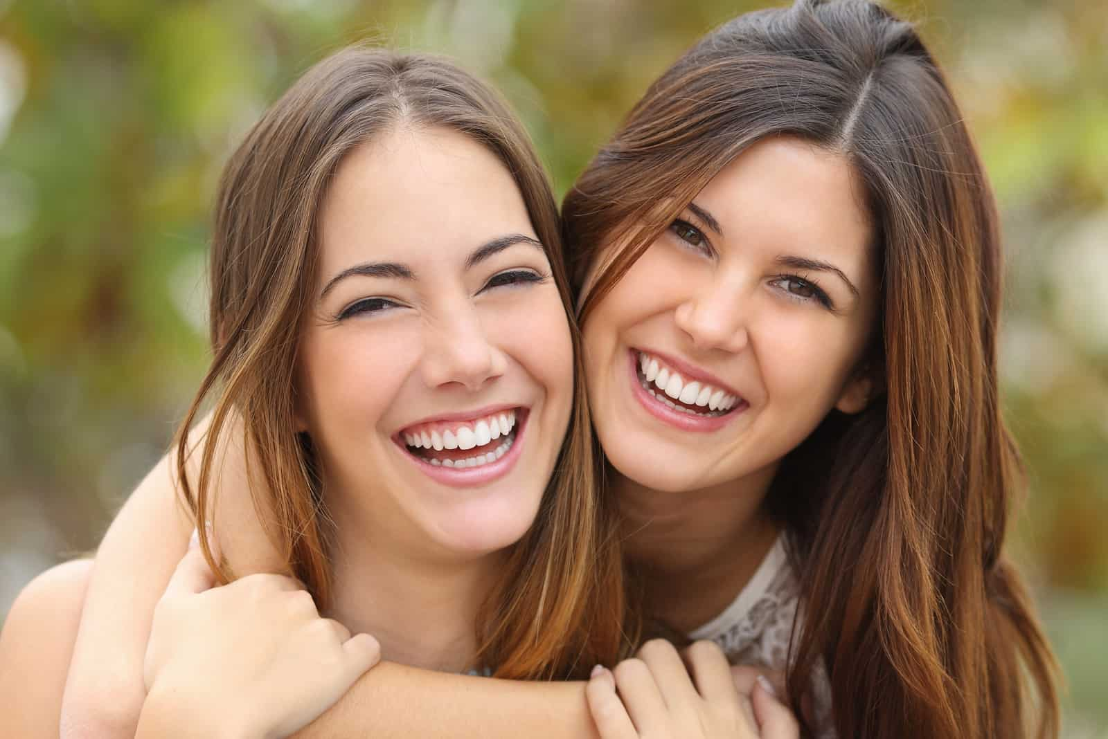 Två kvinnavänner som skrattar med perfekta vita tänder