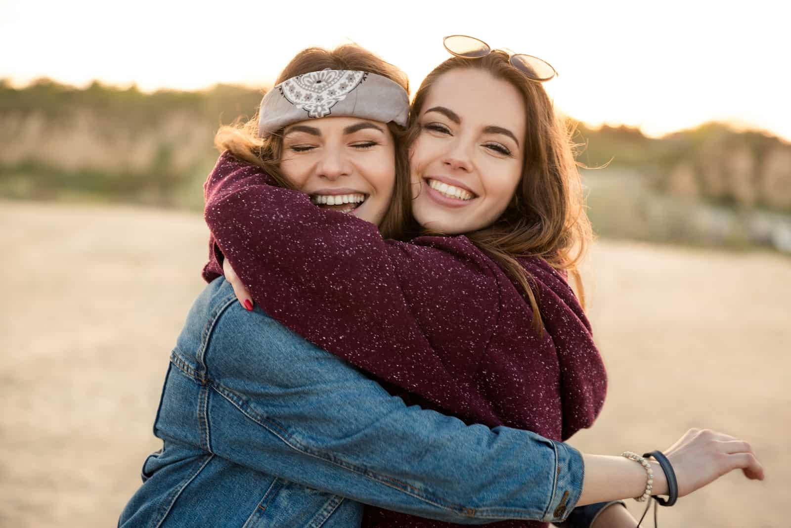 Två le kvinnliga vänner som kramar varandra på stranden