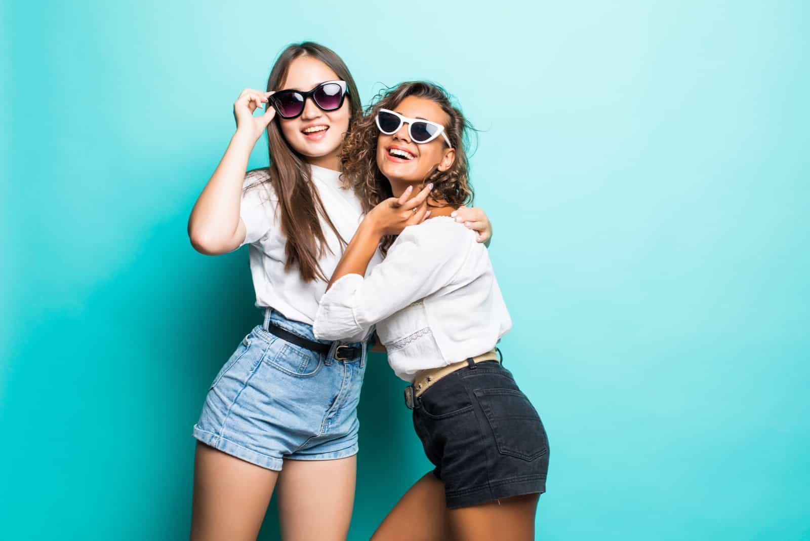 Två söta älskvärda flickvänner i solglasögon poserar