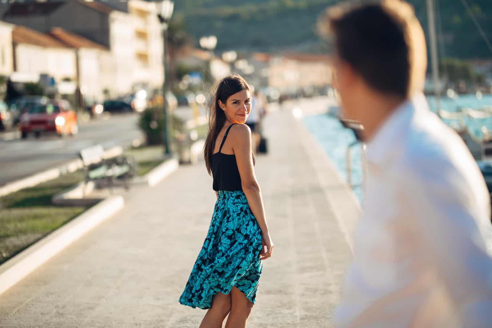 Ung attraktiv kvinna som flörtar med en man på gatan